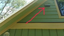 Picture of HRV outdoor-air intake with red arrow for homeowner manual.